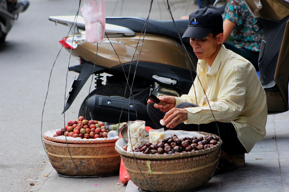 A man selling fruit on the street in the Old Quarter of Hanoi, Vietnam