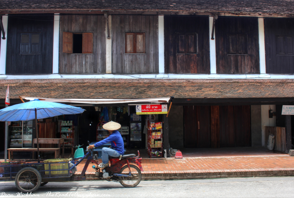 A man on a cart at some old shopfronts in Luang Prabang, Laos