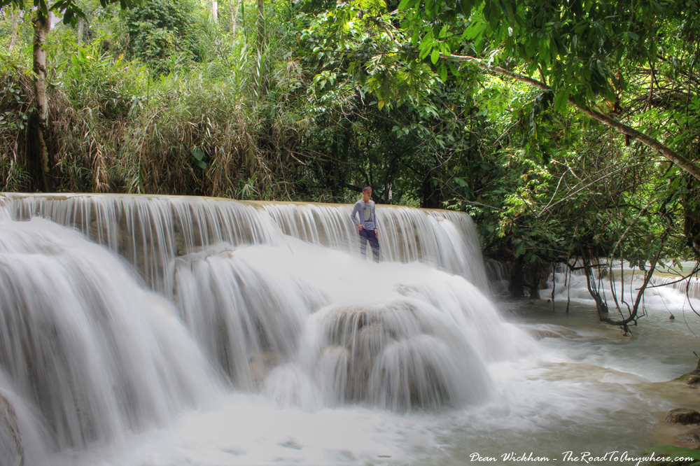 A man standing on a cascade below Kuang Si Waterfall, Laos