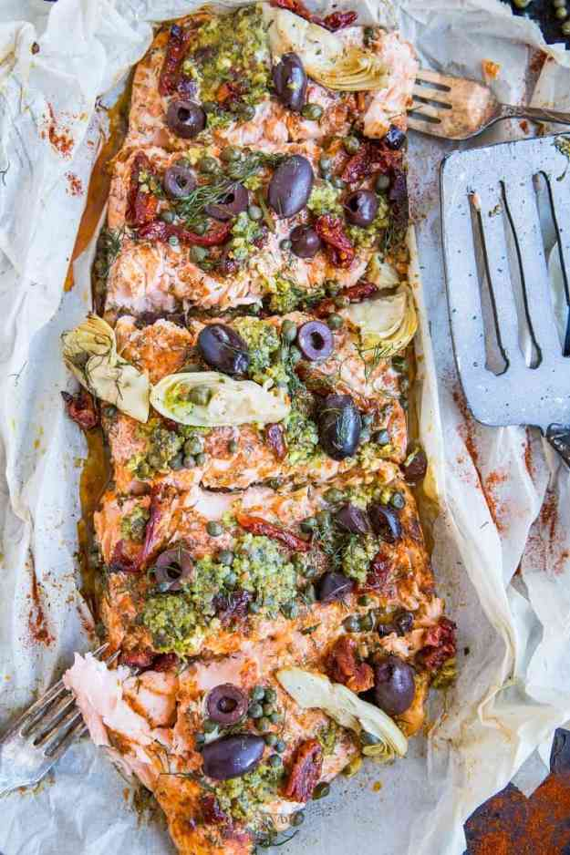 Mediterranean-inspired Salmon in Parchment Paper (or fish en papillote) with sun-dried tomatoes, kalamata olives, dill, capers, and artichoke hearts. This easy dinner recipe is paleo, keto, and packed with flavor!
