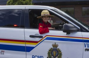 Brayden Woroshelo certainly looks the part, as he takes in the parade from a unique perspective next to his dad RCMP Sergeant Darren Woroshelo. / EVAN MATTHEWS