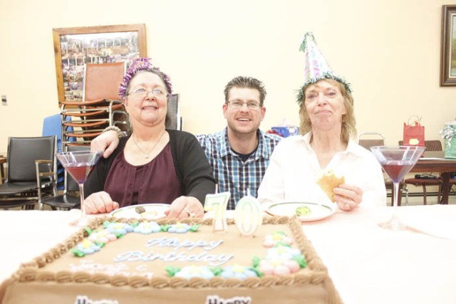 Photo: Evan Matthews Barbara Markham (left) and Jannie Sollows (right) each celebrated their 70th birthdays over the weekend at the Golden Year's Seniors Lodge in Valemount.  Conrad Broersma crouches in between, as he says he couldn't miss the  opportunity to hop in for a photo on the special day.