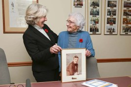 Council Chambers were packed for the swearing-in. Newly-elected Councillor Donnie MacLean stands with her mom Louise MacLean and a photo of her dad Sandy MacLean, Valemount's first mayor. / PHOTOS LAURA KEIL
