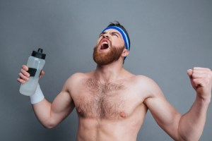 58469565 - furious bearded young sportsman with bottle of water standing and shouting over grey background