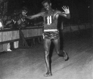 Abebe Bikila running barefoot across the finish line in Rome