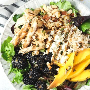 Salad topped with chicken and fruit