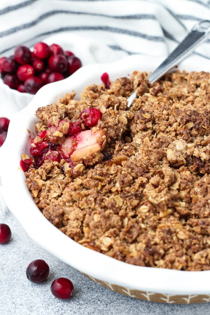 Scooping the cooked cranberry apple pear crisp from the baking dish.
