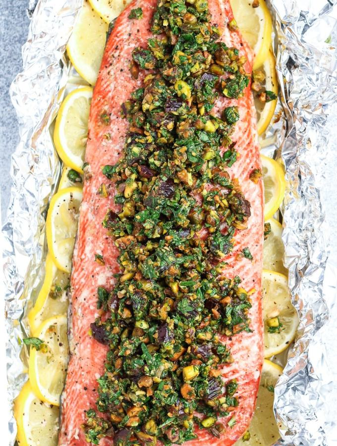Oven baked salmon on a bed of lemons topped with pistachio gremolata