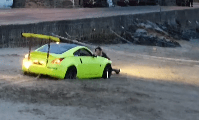 An onlooker also tried to help push the car out of the sand
