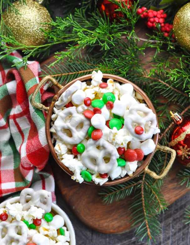 Overhead image of bowl of Christmas snack mix surrounded by decorations