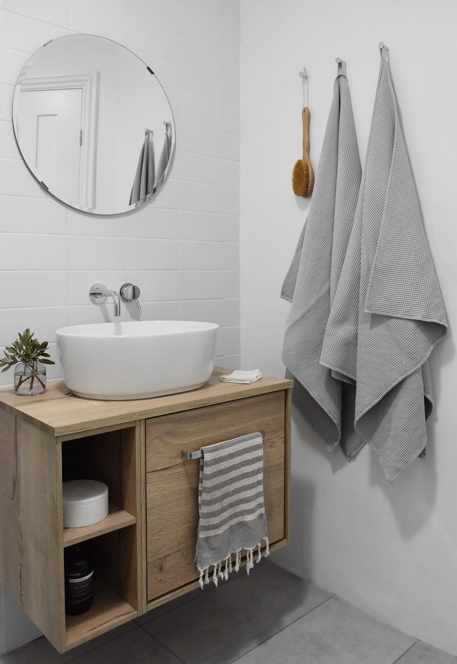 Contemporary minimalist bathroom with white metro tiles, oak vanity unit, countertop sink and circular mirror   How to design a lighting scheme that works for you   These Four Walls blog