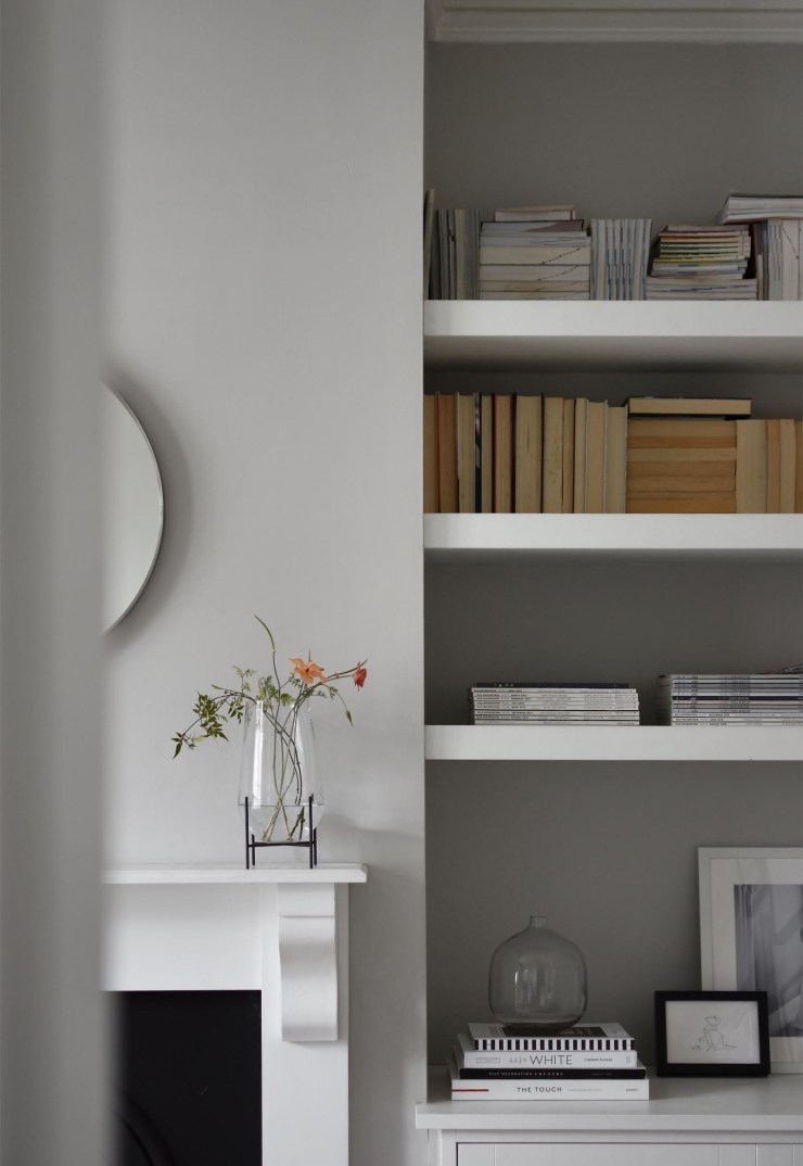 Minimalist grey living room with white fireplace, round mirror and iconic 'Echasse' vase by Menu | The design classics of the future | These Four Walls blog