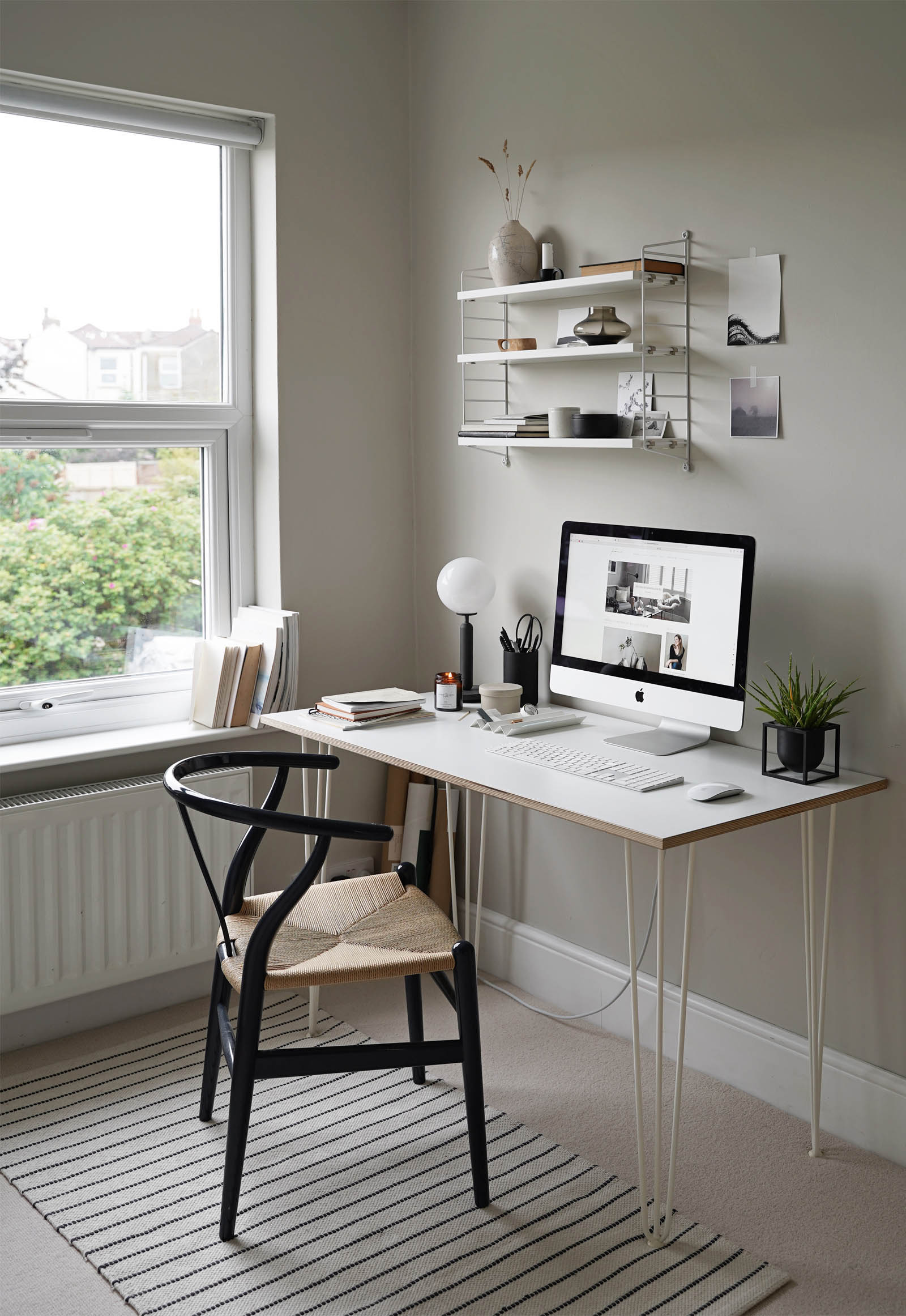 Calming grey home office decor with minimalist desk setup, String Pocket shelving, pale beige carpet and Wishbone chair | These Four Walls blog