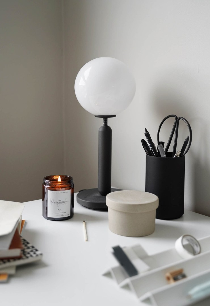 Minimalist desk organisation and contemporary black table lamp in a calming grey home office   These Four Walls blog