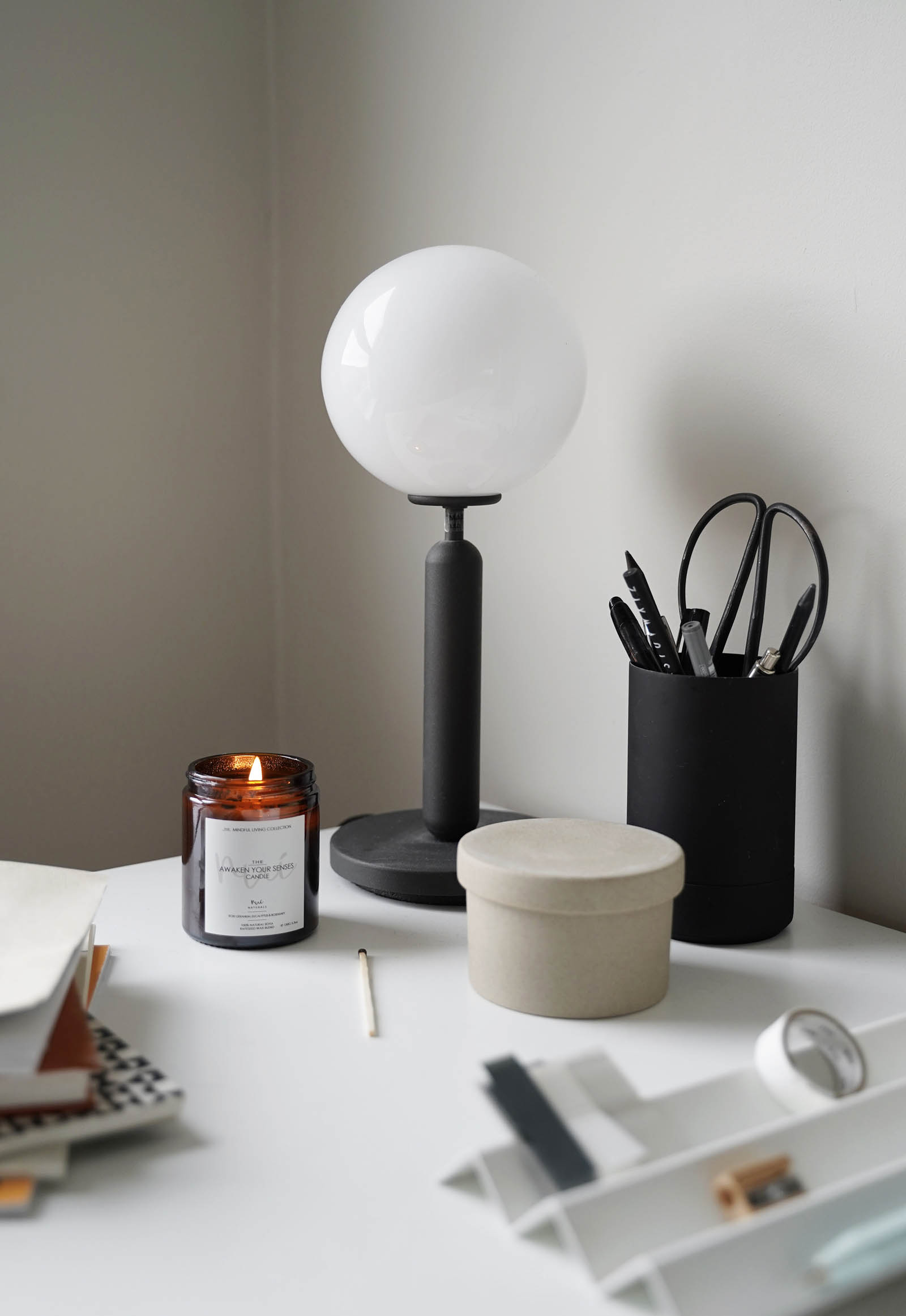 Minimalist desk organisation and contemporary black table lamp in a calming grey home office | These Four Walls blog