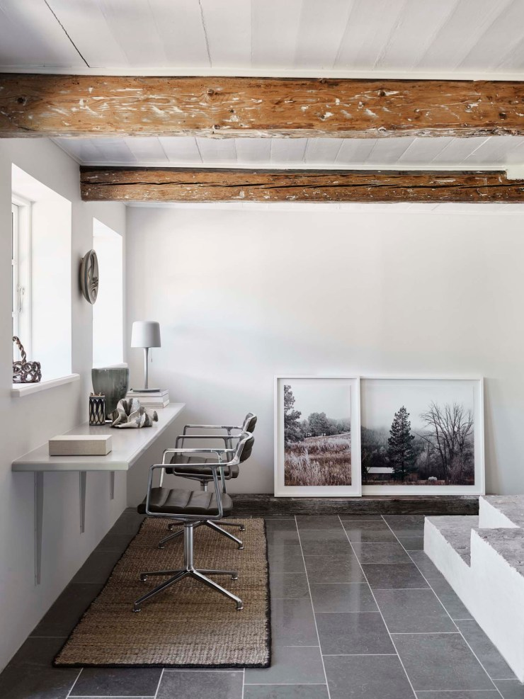 Minimalist home office with white walls, leather chairs and beamed ceiling   The Vipp Farmhouse - a rustic Scandinavian holiday cottage deep in the Danish countryside   These Four Walls blog