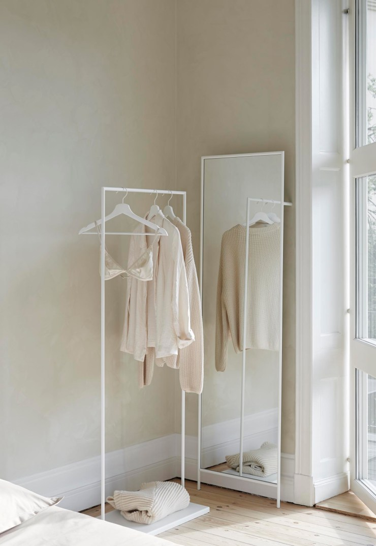 Simple beige bedroom with textured walls, plus minimalist clothes rail and full-length mirror by Design Of | These Four Walls blog