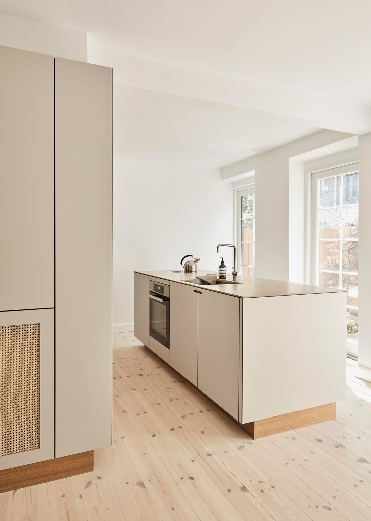 Minimalist beige kitchen with island unit, rattan radiator cover and Jura stone worktops   These Four Walls blog