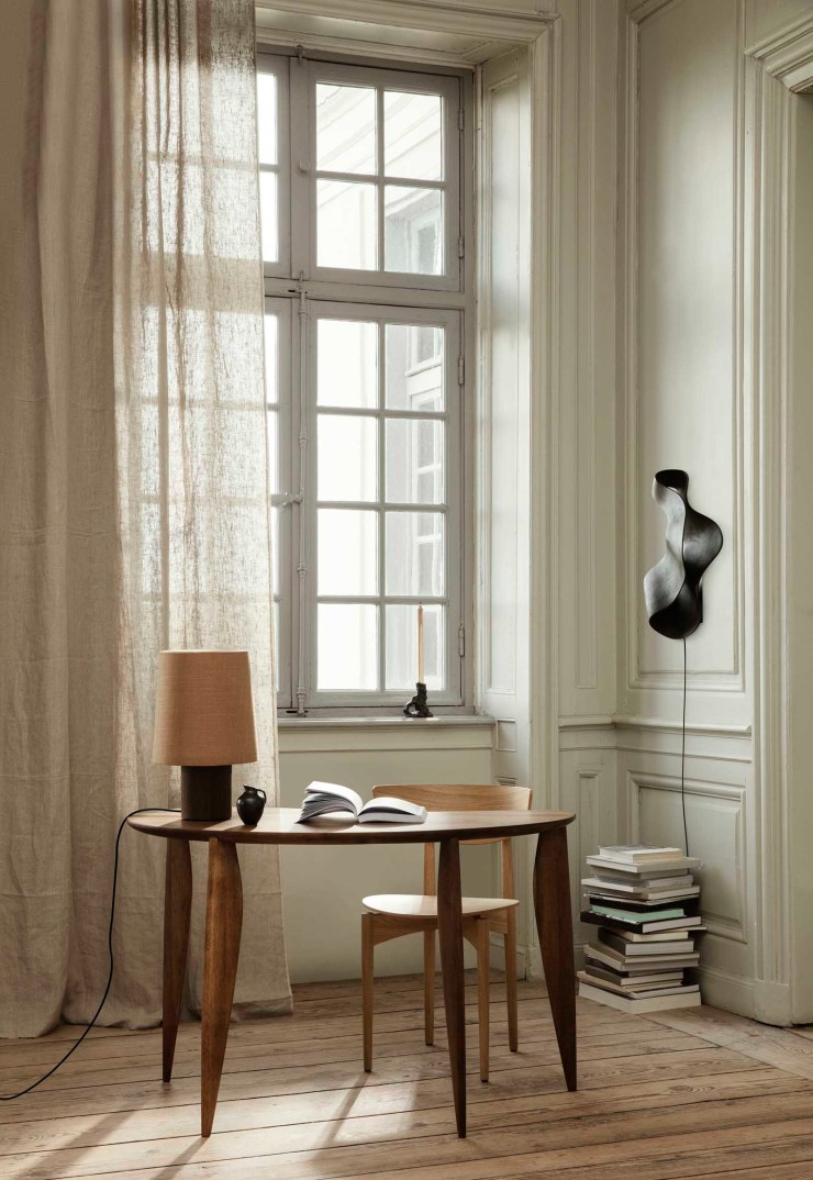 Minimalist home office with beige panelled walls, linen curtain, curved wooden desk and sculptural wall lamp | The autumn-winter 2021 collection from Ferm Living | These Four Walls blog