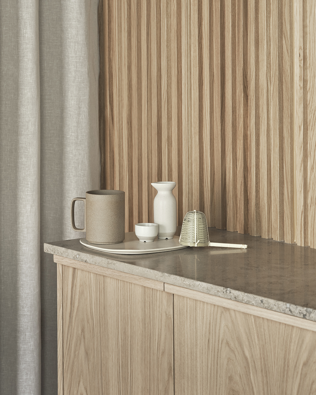 Vertical slatted wall panelling and minimalist kitchen unit in pale oak | Eight inspiring kitchen ideas from Nordiska Kök's new showroom | These Four Walls blog