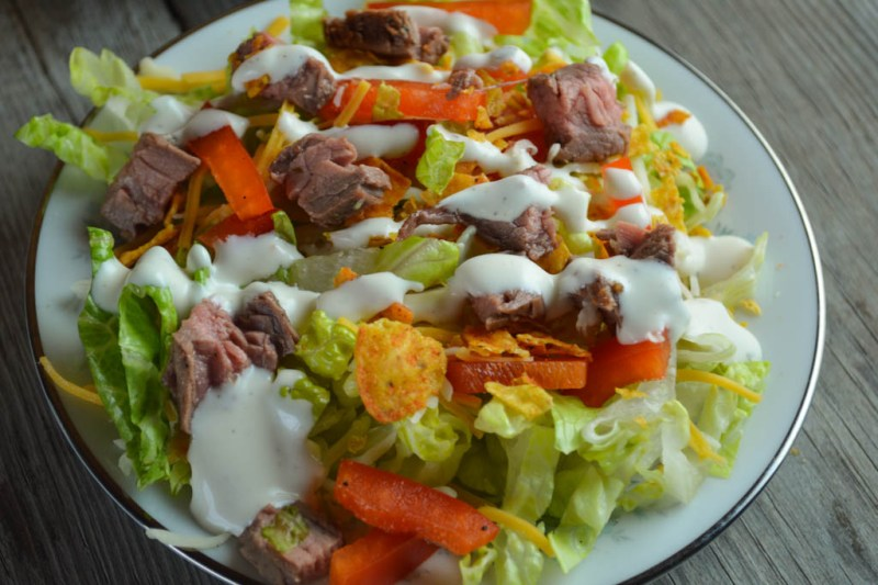 By adding taco seasoning to both the marinade and the dressing, this Flank Steak Salad is a family-pleasing meal with simple additions like Doritos.