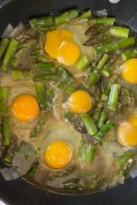 Baked Eggs and Asparagus with Parmesan cheese is an economical meal option for breakfast, lunch or brunch. Made in a large skillet, this old fashioned asparagus meal is quick and easy. Simply adjust the cooking time to get eggs cooked to your liking.