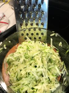 Shred the zucchini and then measure it. No need to squeeze excess moisture out of it.