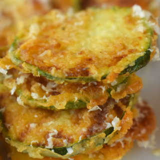 Easy Pan Fried Zucchini is a fast side dish to use up garden zucchini.  These zucchini coins are breaded lightly and pan fried until crispy, salty and delicious. Grate with fresh Parmesan, and serve!