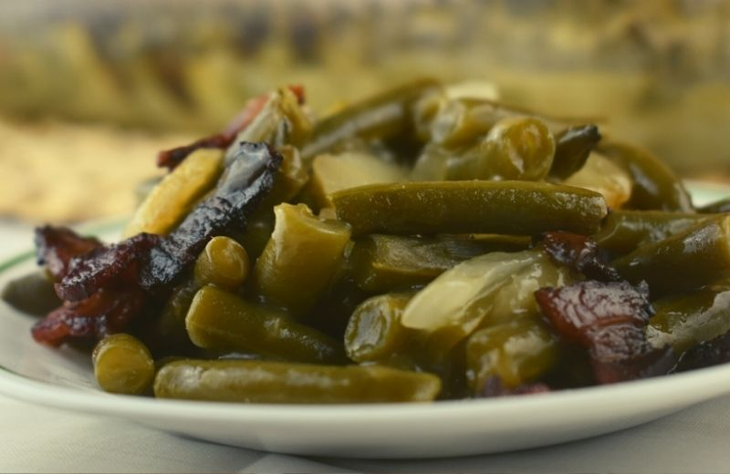 Pennsylvania Dutch Green Beans are a German-inspired side dish. Canned green beans are enhanced with water chestnuts, onions and bacon and baked in a slightly sweet and tangy sauce. These can be eaten right away or prepped the night before for the perfect holiday green bean recipe.