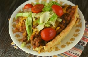 Deep Dish Taco Pie is stuffed full of ground beef, refried beans, cheese and crushed tortilla chips, all nestled in a pie crust. Serve this easy taco pie at your next Taco Tuesday dinner.
