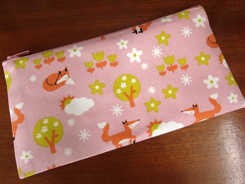 A pencil case featuring dreamy foxes on a pink background