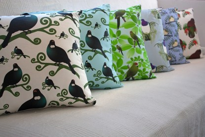 Several cushions featuring NZ native birds displayed on a couch.
