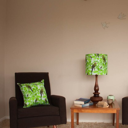 A domestic setting: a cushion featuring kakariki on a brown armchair, and a matching lamp on a coffee table.