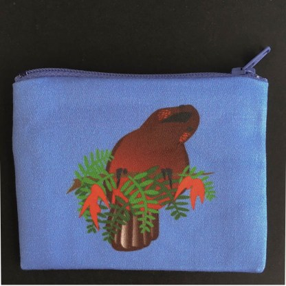 Photograph of kaka coin purse. The purse is a mid blue colour, with an illustration of a kaka holding a swarth of kōwhai ngutukākā leaves and flowers.