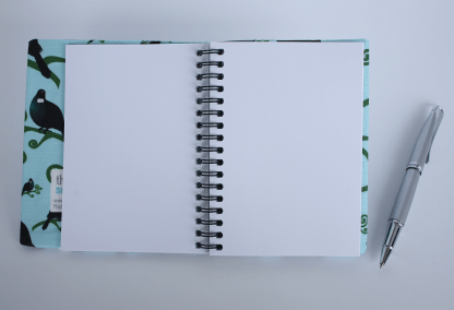 Product photograph showing the visual diary laying open, with a pen at the side for context.
