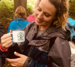 woman outdoors holding SHAC mug