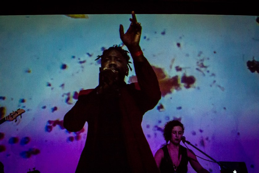 Mykele Deville performs onstage, with a mic in one hand and his other hand raised reverently. Behind him is a blue and purple screen and Emilie Modaff on keys