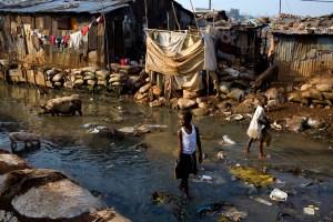 Boy walks in the river in Kroo Bay slum looking for scrap metal to sell. Kroo Bay, Freetown, Sierra Leone.