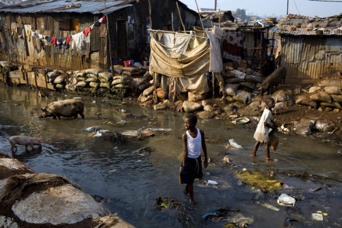A boy walks through the river in Kroo Bay slum looking for scrap metal to sell. The river is effectively a giant sewage and everyday new garbage arrives in the water from the hills around. Kroo Bay, Freetown, Sierra Leone.