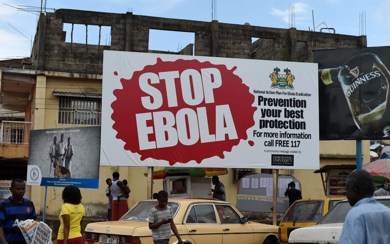 "(FILES) This file picture dated November 7, 2014 shows people walking past a billboard reading ""Stop Ebola"" in Freetown. Sierra Leone said on March 19, 2015 it will confine around 2.5 million people to their homes across the capital and in the north in a three-day shutdown aimed at stemming the Ebola epidemic. AFP PHOTO/ FRANCISCO LEONGFRANCISCO LEONG/AFP/Getty Images"