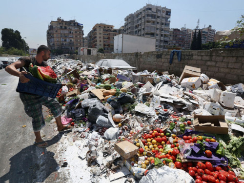A Lebanese man throws more trash on a pile of garbage covered with white pesticide in the Palestinian refugee camp of Sabra in Beirut, Lebanon, Thursday, July 23, 2015. The Lebanese cabinet has failed to agree on a solution for the countryís growing garbage crisis, postponing discussion until next week as trash piles up on the streets. (AP Photo/Bilal Hussein)