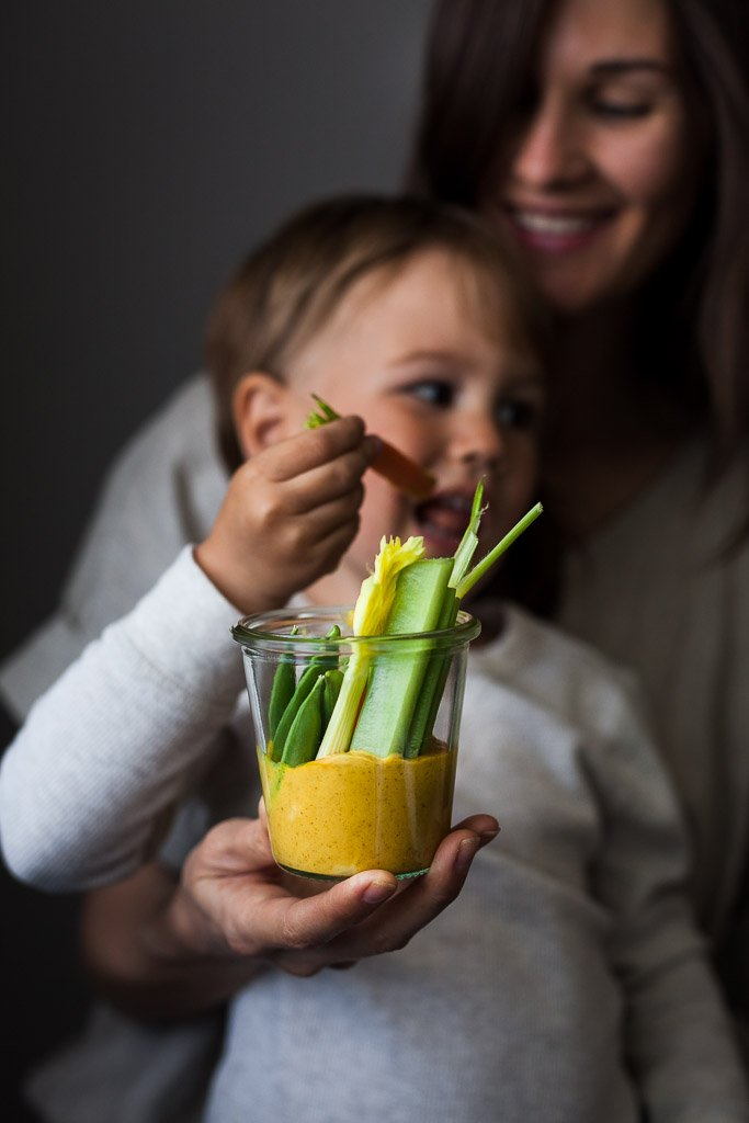 Mother and son smiling enjoying a snack jar with gold dip from Little Green Kitchen.