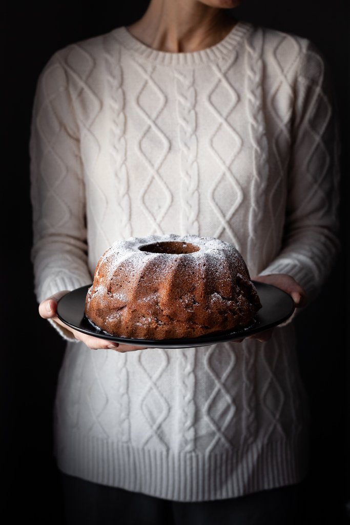 head on image of vegan apple spice cake in bakers hands.