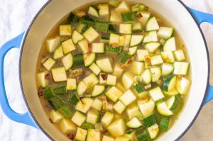 Zucchini with spices in stock in a dutch oven