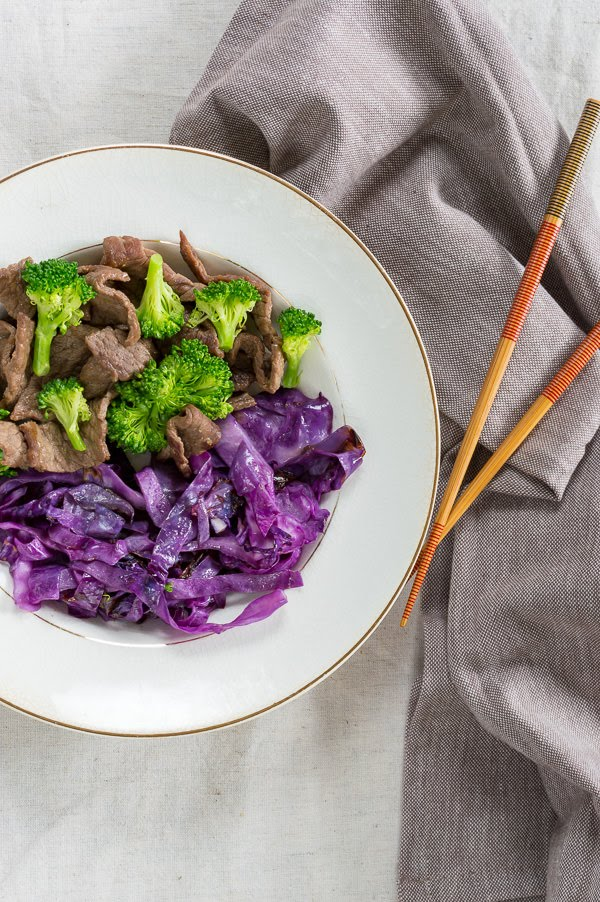broccoli beef in a bowl with purple cabbage and chop sticks