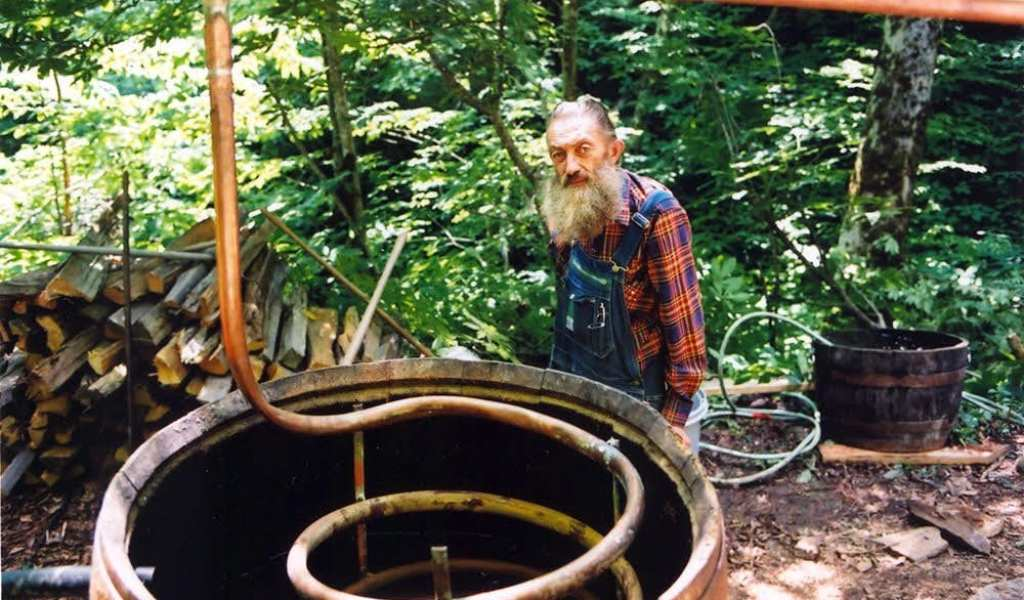 Popcorn Sutton poses with one of his moonshine stills (photo courtesy of https://suckerpunchpictures.com/)