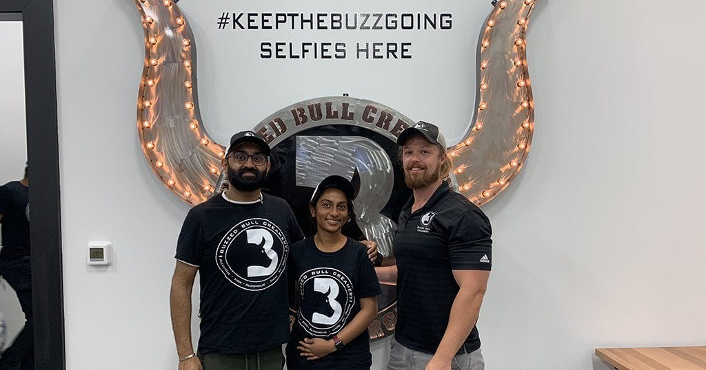 Husband and wife duo and co-owners of the Pigeon Forge Buzzed Bull Creamery Shiv and Mishika Patel pose with Colten Mounce, Buzzed Bull CEO in front of the #KeepTheBuzzGoing 3D selfie mural (photo by Morgan Overholt/TheSmokies.com)
