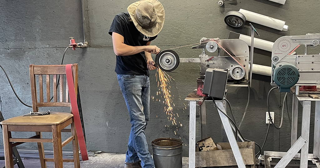 A professional helps a guest make a knife in Pigeon Forge