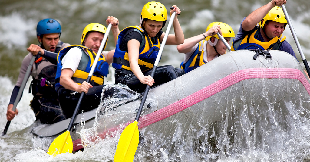Group of people whitewater rafting on a river