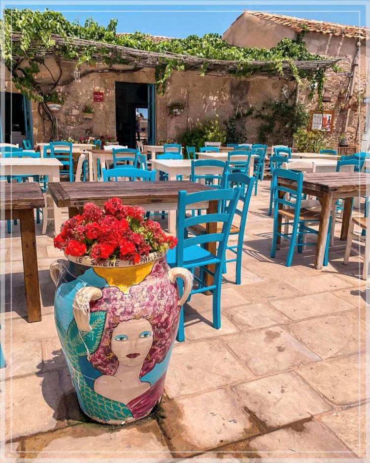 A Sicilian vase and blue chairs at a restaurant in Marzamemi